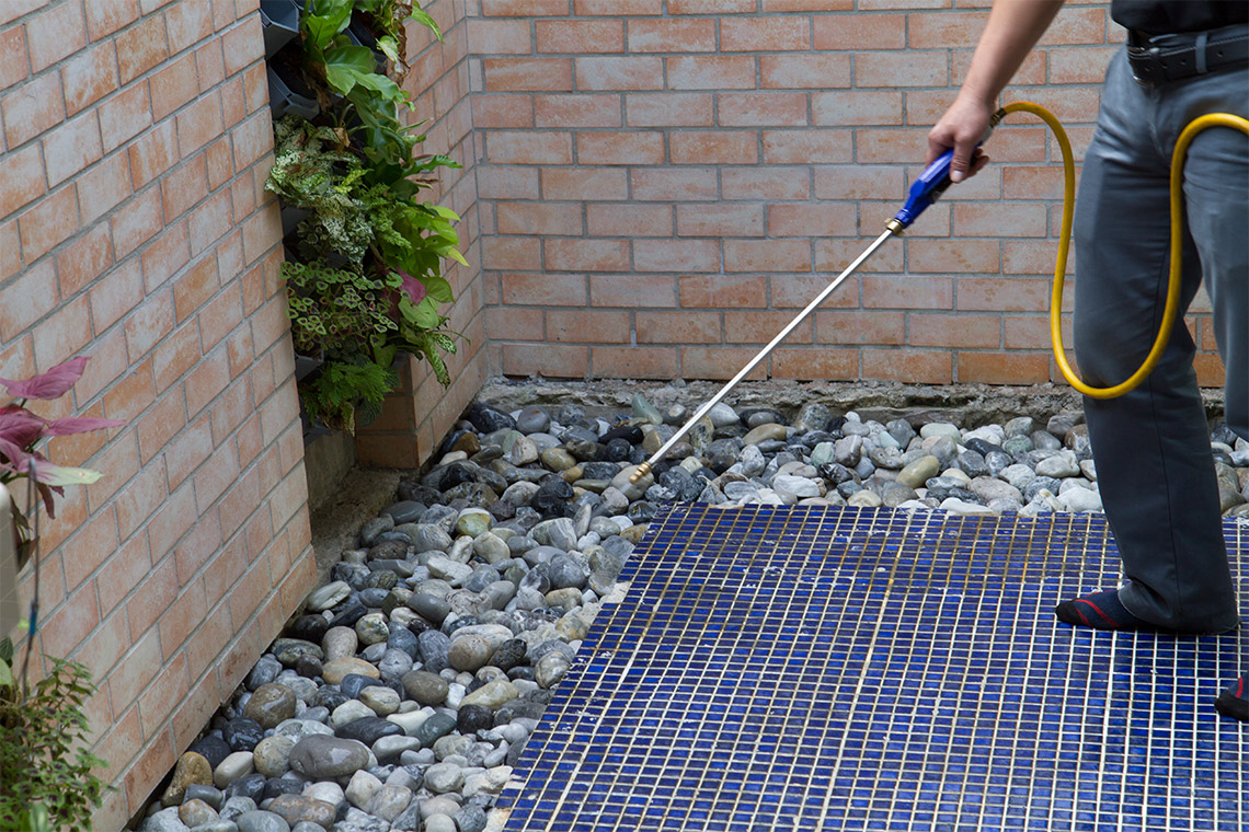Man spraying rocks in a back patio