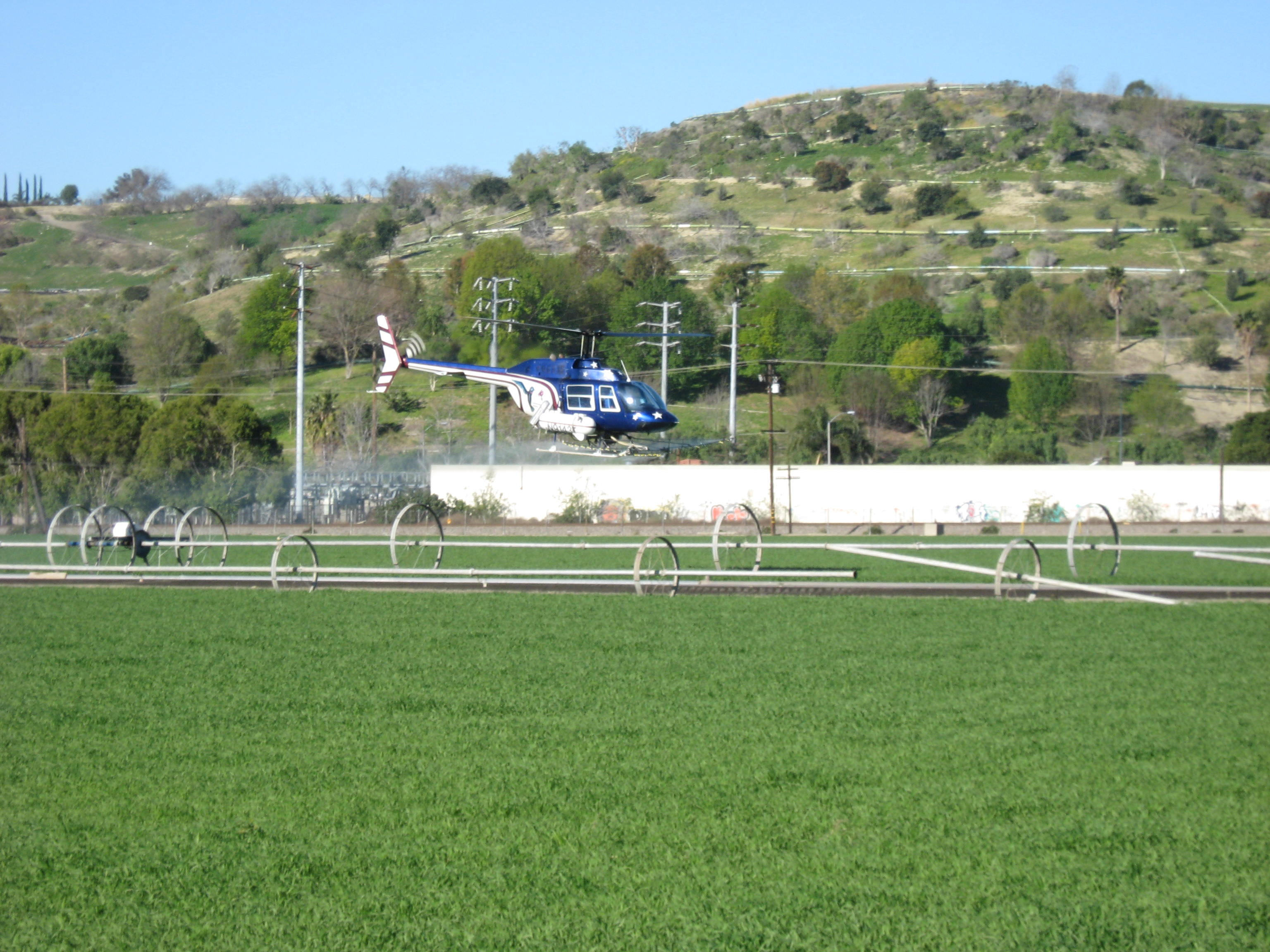 Helicopter hovering to spray field
