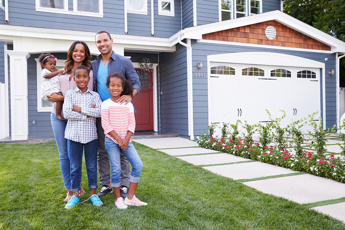 Happy family posing in front of a nice house